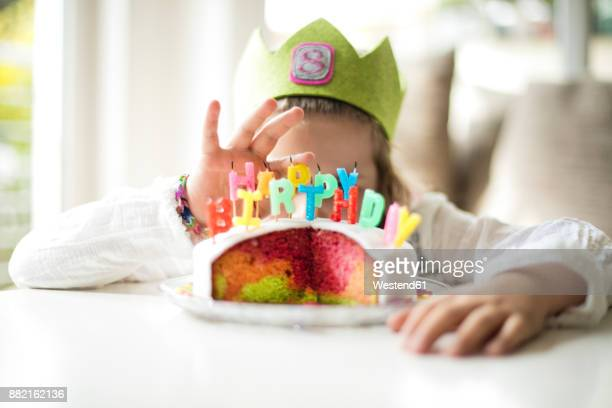 girl hiding behind birthday cake - happybirthdaycrown stock pictures, royalty-free photos & images