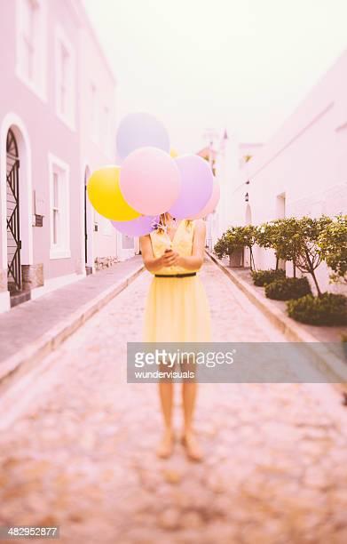 Fille se cacher derrière des ballons colorés