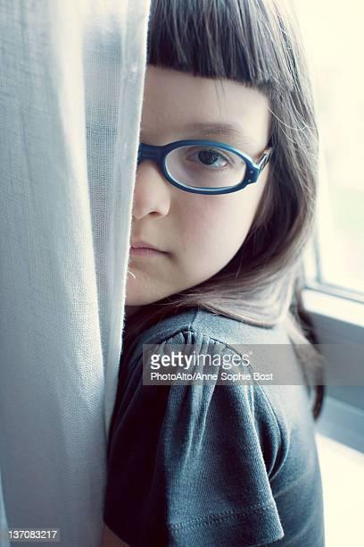 Girl hiding behind curtain