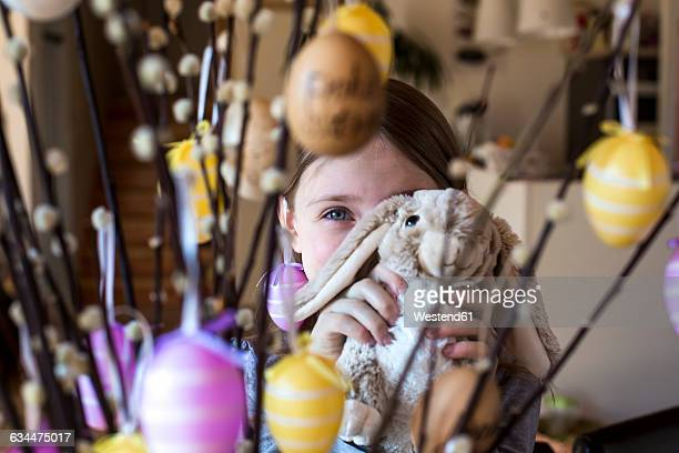 girl hiding behind easter bunny and twigs of pussy willows decorated with easter eggs - easter bunny stock pictures, royalty-free photos & images