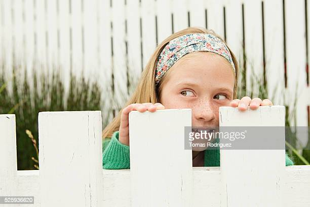 Girl (8-9) hiding behind fence