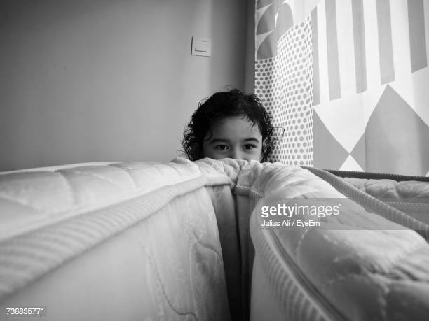 Girl Hiding Behind Mattress
