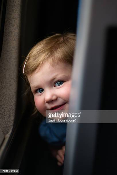 Girl hiding behind seat on train