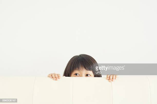 Girl hiding behind sofa