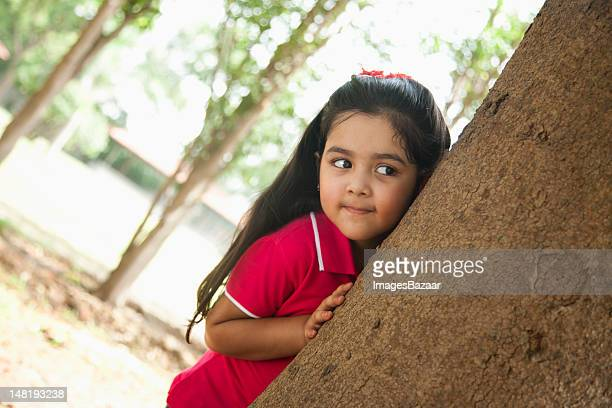 Girl (4-5) hiding behind tree