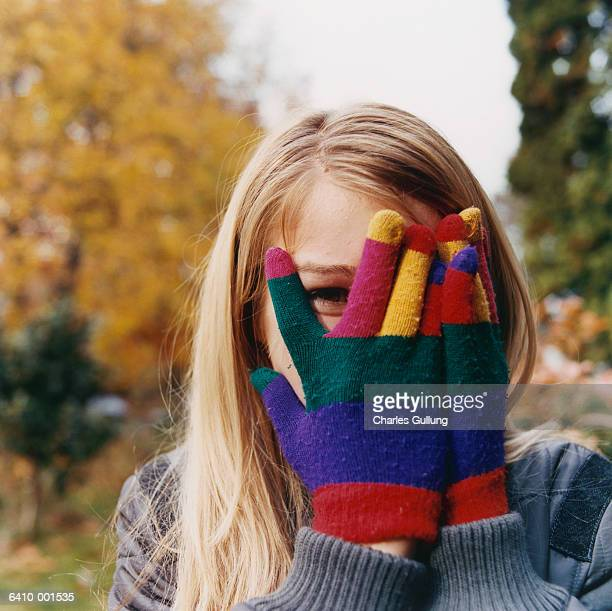 girl hiding face behind gloves - teenagers only stock pictures, royalty-free photos & images