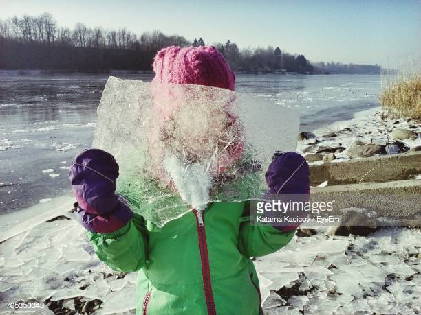 Girl Hiding Face With Ice While Standing By Frozen River