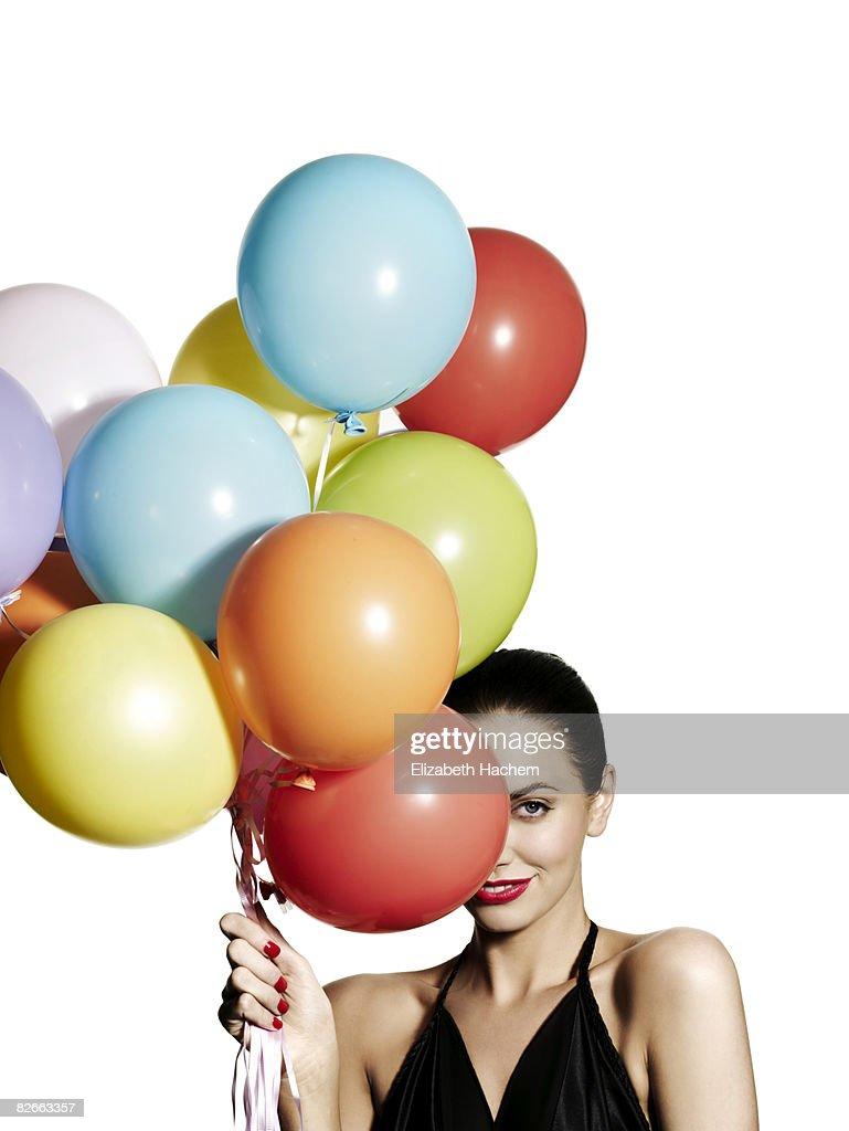 Girl hiding one eye behind a bunch of balloons : Stock Photo