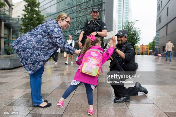 A girl 'high fives' an armed police officer on the Hayes in Cardiff City centre on May 29 2017 in Cardiff Wales Preparations are underway for the...