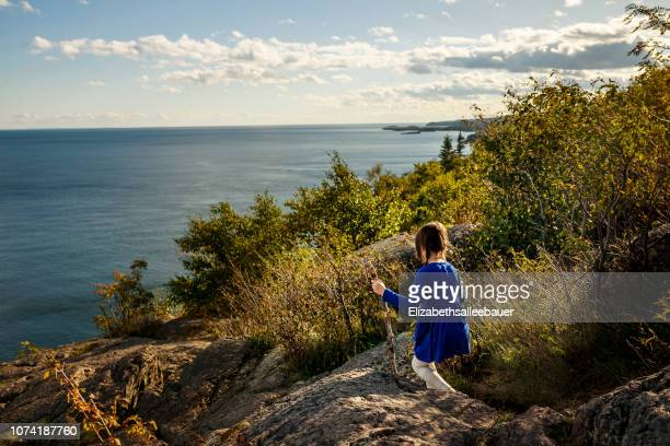 girl hiking across rocks, lake superior provincial park, united states - lake superior provincial park stock pictures, royalty-free photos & images