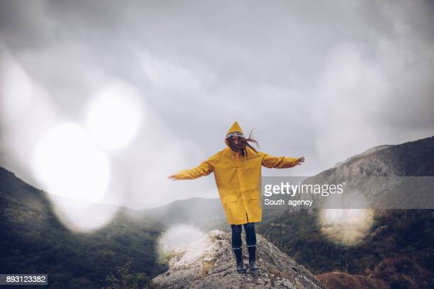 girl hiking alone on mountain - raincoat stock pictures, royalty-free photos & images