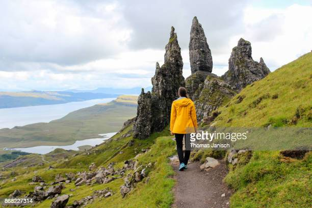 Girl hiking towards The Old Man of Storr, Scotland