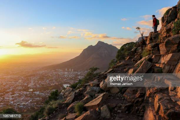 girl hiking up lion's head during sunrise, cape town, south africa - table mountain stock pictures, royalty-free photos & images