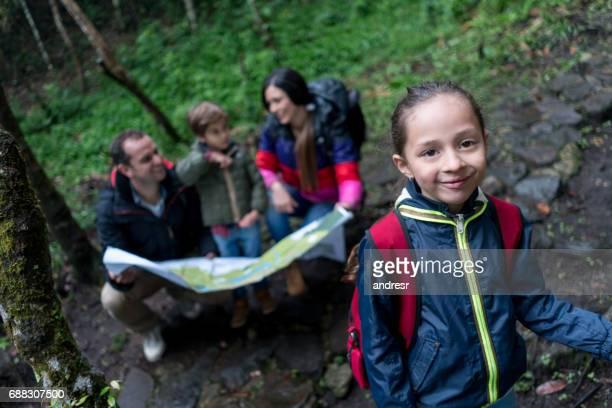 Niña va de excursión con su familia y mirando un mapa