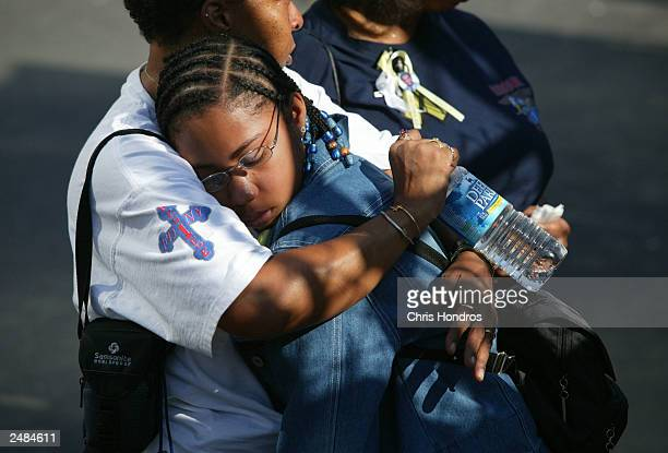 A girl his hugged by a woman during a memorial for victims of the 9/11 terrorist attacks September 11 2003 in New York City New York marked the...
