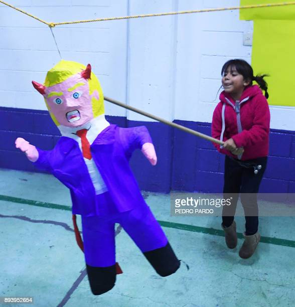 A girl hits a pinata with the figure of US President Donald Trump during a traditional posada in Mexico City on December 16 2017 The Posadas is a...