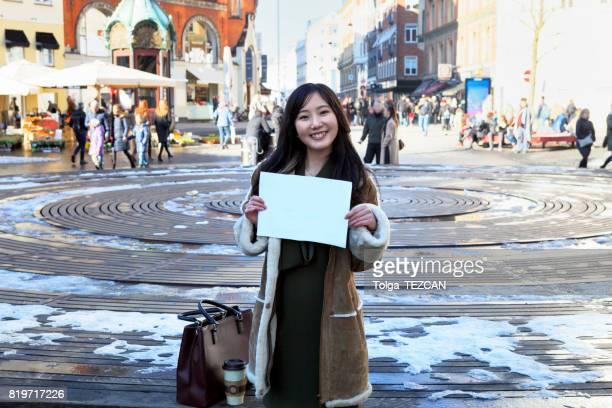 Girl hold white blank paper.
