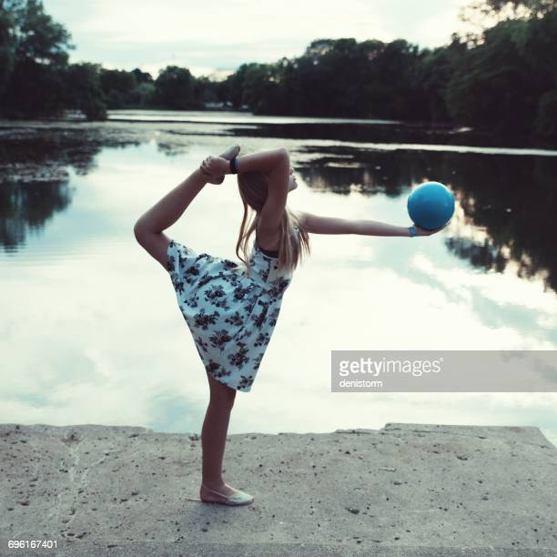 girl holding a ball standing on one leg in ring pose