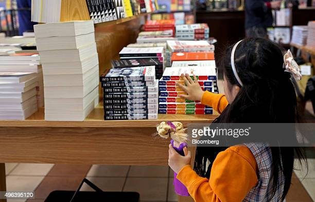 A girl holding a Barbie doll looks at books displayed for sale at a Barnes Noble Inc store at Union Square in the Manhattan borough of New York US on...
