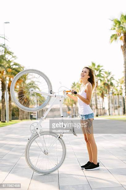 Girl Holding a Bicycle and Laughing