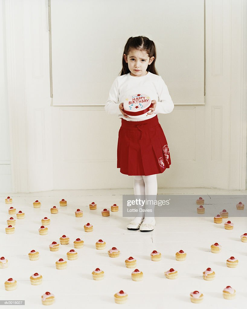 Girl Holding a Birthday Cake Surrounded by Other Cakes : Stock Photo
