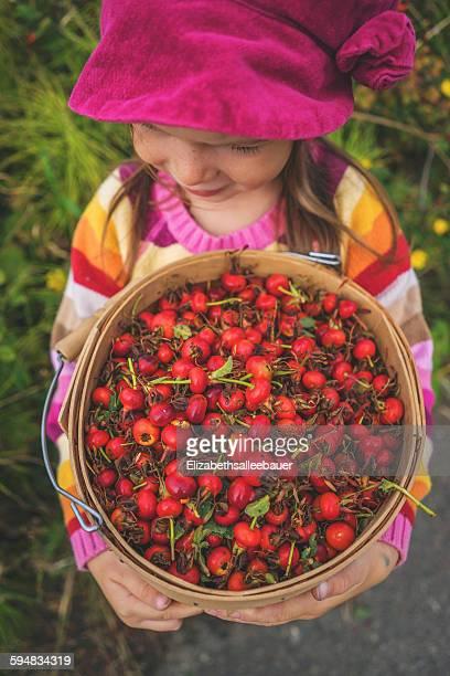 Girl holding a bucket of freshly picked rosehips