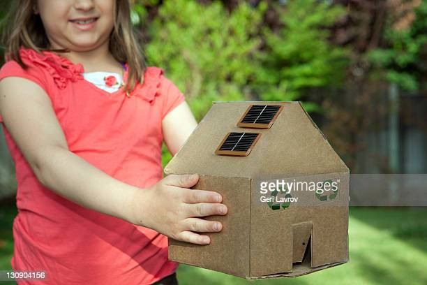 Girl holding a cardboard house with solar panels