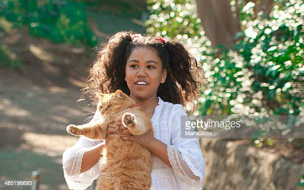girl holding a cat and smiling. - mamigibbs stock photos and pictures