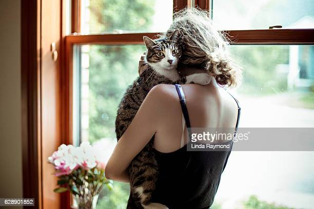girl holding a cat by a window