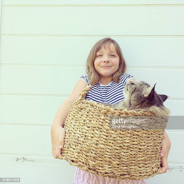 Girl Holding a Cat in a Basket