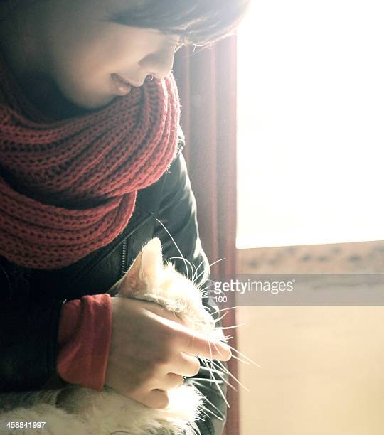 girl holding a cat in her arms