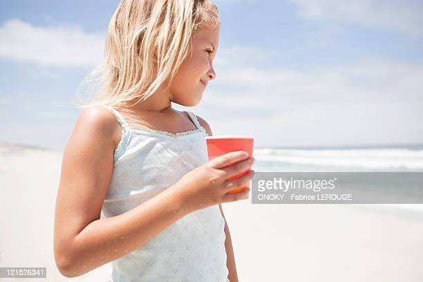 Girl holding a disposable glass on the beach