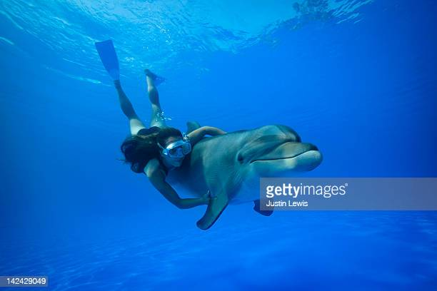 Girl holding a dolphin with fins diving udnerwater