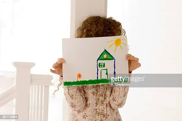 Girl holding a drawing sheet in front of her face