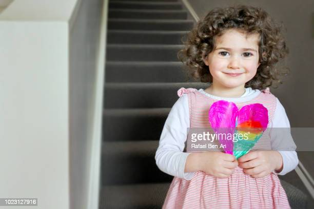 girl holding a gift card in the shape of a heart for father's day / mother's day - rafael ben ari foto e immagini stock