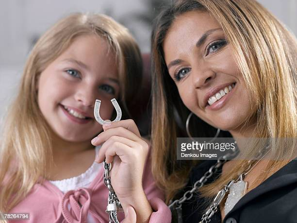girl holding a horse shoe locket on her mother's necklace and smiling - portafortuna foto e immagini stock