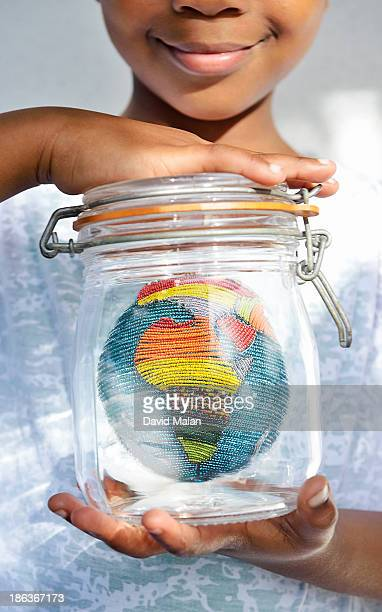 Girl holding a jar with a beaded globe inside