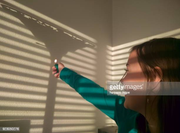 Girl holding a lighter pretending to light a shadow of a lamp.