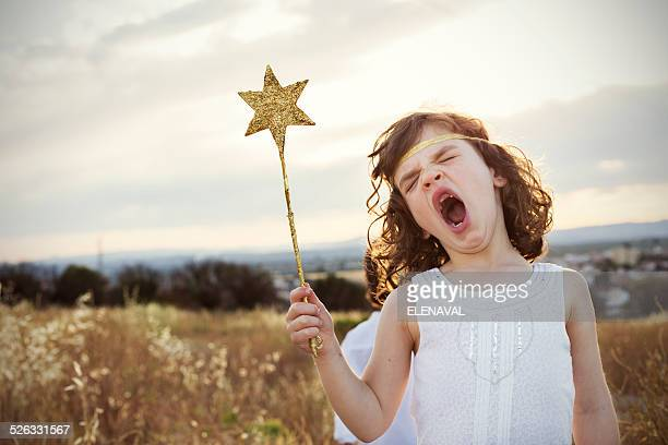 Girl holding a magic wand yawning