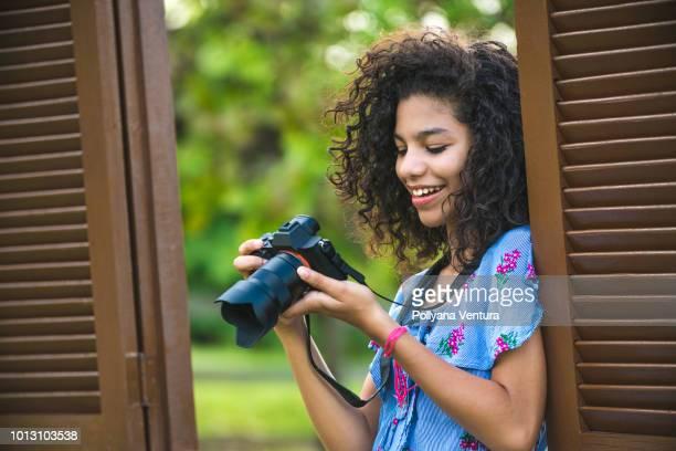 menina, segurando uma câmera fotográfica na janela - camera girls - fotografias e filmes do acervo