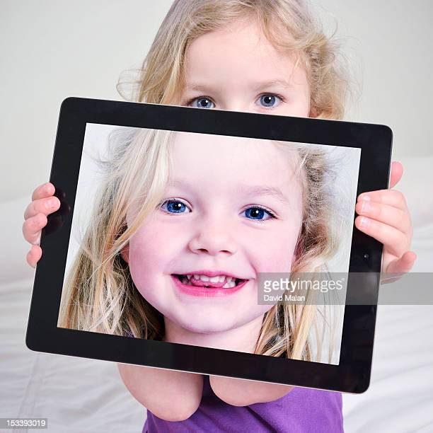 Girl holding a picture of herself on an e-tablet
