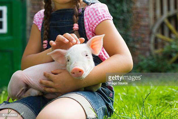 A girl holding a piglet