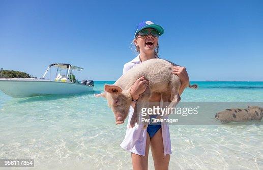 A girl holding a piglet_swimming pigs_Exumas_Bahamas