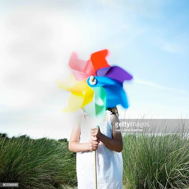 Girl Holding a Pinwheel in sea grass & sand dunes