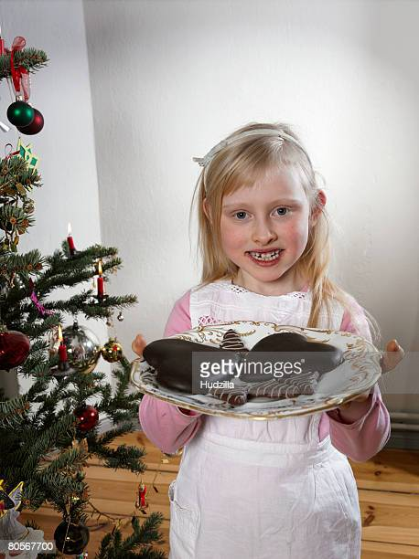 A girl holding a plate of cookies at Christmas