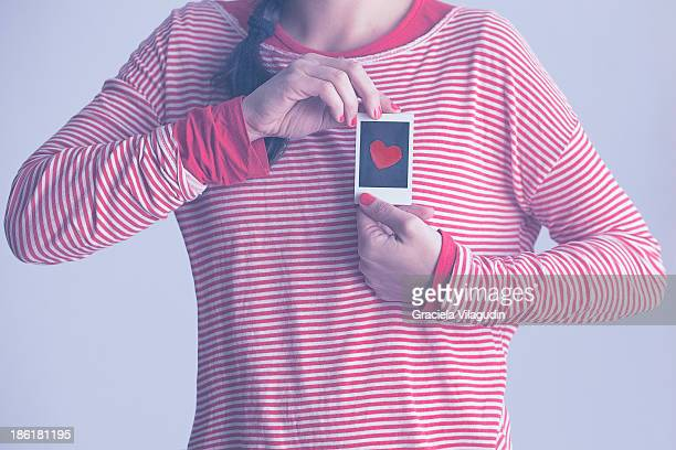 girl holding a polaroid photo with a heart - printed sleeve stock pictures, royalty-free photos & images