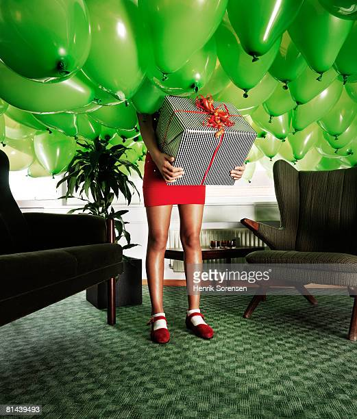 girl holding a present in a room filled with baloons - under skirt stock photos and pictures