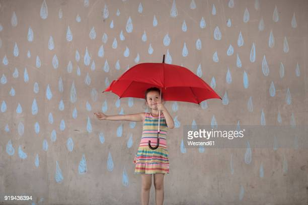 Girl holding a red umbrella standing next to a concrete wall with rain drop chalk drawings