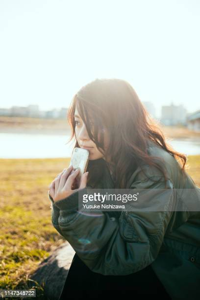 girl holding a smartphone and staring into the distance - yusuke nishizawa photos et images de collection