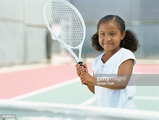 girl holding a tennis racket in a tennis court